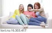 Купить «Three smiling teenage girls watching tv at home», видеоролик № 6303417, снято 8 мая 2014 г. (c) Syda Productions / Фотобанк Лори