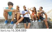Купить «Group of smiling teenagers hanging out outdoors», видеоролик № 6304089, снято 12 августа 2014 г. (c) Syda Productions / Фотобанк Лори