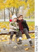 Маленький мальчик обнимает девочку с розой на скамейке в осеннем парке. Стоковое фото, фотограф Юлия Кузнецова / Фотобанк Лори
