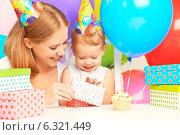 Купить «Детский день рождения. Мама и маленькая дочь открывают подарок», фото № 6321449, снято 24 августа 2014 г. (c) Евгений Атаманенко / Фотобанк Лори