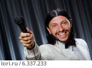 Купить «Man singing in front of curtain in karaoke concept», фото № 6337233, снято 14 июля 2014 г. (c) Elnur / Фотобанк Лори