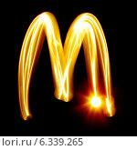 Купить «Светящаяся буква M на черном фоне», иллюстрация № 6339265 (c) Роман Сигаев / Фотобанк Лори