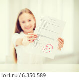 Купить «smiling little student girl with test and A grade», фото № 6350589, снято 7 августа 2013 г. (c) Syda Productions / Фотобанк Лори