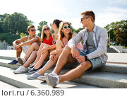 Купить «group of smiling friends sitting on city street», фото № 6360989, снято 20 июля 2014 г. (c) Syda Productions / Фотобанк Лори