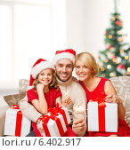 Купить «smiling family holding gift boxes and sparkles», фото № 6402917, снято 26 октября 2013 г. (c) Syda Productions / Фотобанк Лори