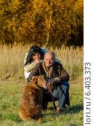Купить «Cheerful couple with dog in autumn countryside», фото № 6403373, снято 31 октября 2013 г. (c) CandyBox Images / Фотобанк Лори