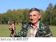 Счастливый пожилой грибник нашел гриб подберезовик на фоне леса. Стоковое фото, фотограф Яна Королёва / Фотобанк Лори