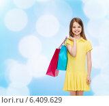 Купить «smiling little girl in dress with shopping bags», фото № 6409629, снято 30 апреля 2014 г. (c) Syda Productions / Фотобанк Лори