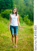 Купить «Симпатичная юная девушка стоит на лесной тропинке», эксклюзивное фото № 6410601, снято 6 июля 2014 г. (c) Игорь Низов / Фотобанк Лори