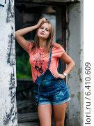 Купить «Симпатичная девушка в шортах стоит возле двери старого здания», эксклюзивное фото № 6410609, снято 17 июля 2014 г. (c) Игорь Низов / Фотобанк Лори