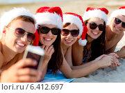 Купить «group of friends in santa hats with smartphone», фото № 6412697, снято 3 августа 2014 г. (c) Syda Productions / Фотобанк Лори
