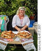 Веселая женщина в народном костюме продает выпечку на ярмарке народного творчества (2014 год). Редакционное фото, фотограф Ирина Борсученко / Фотобанк Лори