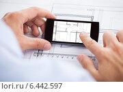 Купить «Architect Analyzing Blueprint On Mobilephone», фото № 6442597, снято 25 марта 2014 г. (c) Андрей Попов / Фотобанк Лори