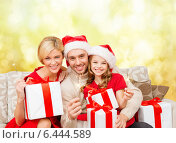 Купить «smiling family holding gift boxes and sparkles», фото № 6444589, снято 26 октября 2013 г. (c) Syda Productions / Фотобанк Лори