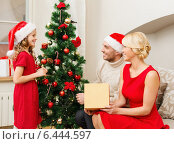 Купить «smiling family decorating christmas tree», фото № 6444597, снято 26 октября 2013 г. (c) Syda Productions / Фотобанк Лори