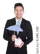Купить «Businessman Sheltering Piggybank With Umbrella», фото № 6445149, снято 11 мая 2014 г. (c) Андрей Попов / Фотобанк Лори