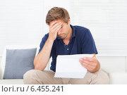Купить «Stressed Man Holding Bill At Home», фото № 6455241, снято 12 июня 2014 г. (c) Андрей Попов / Фотобанк Лори
