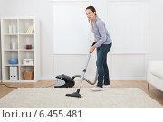 Купить «Woman Vacuuming Rug At Home», фото № 6455481, снято 12 июня 2014 г. (c) Андрей Попов / Фотобанк Лори
