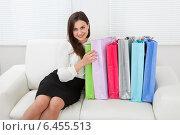 Купить «Businesswoman With Multicolored Shopping Bags Sitting On Sofa», фото № 6455513, снято 12 июня 2014 г. (c) Андрей Попов / Фотобанк Лори