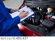 Купить «Mechanic Holding Clipboard In Front Of Open Car Engine», фото № 6459437, снято 18 января 2014 г. (c) Андрей Попов / Фотобанк Лори
