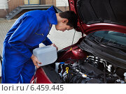 Купить «Mechanic Pouring Antifreeze Into Windscreen Water Tank», фото № 6459445, снято 18 января 2014 г. (c) Андрей Попов / Фотобанк Лори