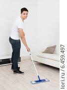 Купить «Young Man Mopping Floor At Home», фото № 6459497, снято 18 января 2014 г. (c) Андрей Попов / Фотобанк Лори