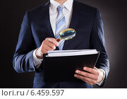 Купить «Businessman Examining Documents With Magnifying Glass», фото № 6459597, снято 10 апреля 2014 г. (c) Андрей Попов / Фотобанк Лори