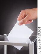 Купить «Businessman Inserting Ballot In Box On Desk», фото № 6459601, снято 10 апреля 2014 г. (c) Андрей Попов / Фотобанк Лори