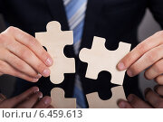 Купить «Businessman Joining Puzzle Pieces At Desk», фото № 6459613, снято 10 апреля 2014 г. (c) Андрей Попов / Фотобанк Лори