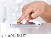 Купить «Man Touching Smartphone At Table», фото № 6459997, снято 10 апреля 2014 г. (c) Андрей Попов / Фотобанк Лори