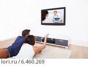 Купить «Couple Watching TV At Home», фото № 6460269, снято 9 марта 2014 г. (c) Андрей Попов / Фотобанк Лори