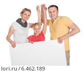 Купить «Happy Young Family Holding Banner», фото № 6462189, снято 20 июля 2014 г. (c) Андрей Попов / Фотобанк Лори
