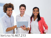 Купить «Three colleagues working on tablet pc smile to camera», фото № 6467213, снято 16 февраля 2019 г. (c) Wavebreak Media / Фотобанк Лори