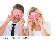 Купить «Attractive young couple holding pink hearts over eyes», фото № 6480845, снято 29 апреля 2014 г. (c) Wavebreak Media / Фотобанк Лори