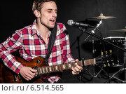 Купить «Man with guitar during concert», фото № 6514565, снято 18 февраля 2013 г. (c) Elnur / Фотобанк Лори
