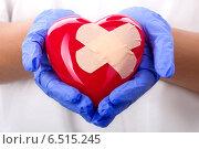 Купить «Руки врача в синих перчатках держат заклеенное пластырем сердце», фото № 6515245, снято 20 июня 2014 г. (c) Людмила Дутко / Фотобанк Лори