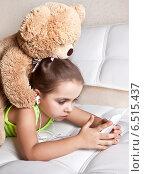 Купить «Девочка в наушниках с игрушечным медведем смотрят в мобильный телефон», фото № 6515437, снято 9 октября 2014 г. (c) Элина Гаревская / Фотобанк Лори