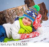 Маленький мальчик в зимней вязаной одежде лежит на снегу. Стоковое фото, фотограф Максим Топчий / Фотобанк Лори