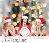 Купить «smiling women in santa helper hat with clock», фото № 6524397, снято 20 октября 2013 г. (c) Syda Productions / Фотобанк Лори