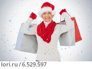 Festive woman smiling at camera holding shopping bags. Стоковое фото, агентство Wavebreak Media / Фотобанк Лори