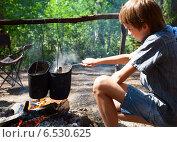 Купить «Мальчик готовит еду на костре», фото № 6530625, снято 31 июля 2014 г. (c) Дмитрий Наумов / Фотобанк Лори