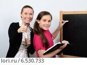 Улыбающиеся девочка и учительница возле школьной доски. Стоковое фото, фотограф VIACHESLAV KRYLOV / Фотобанк Лори