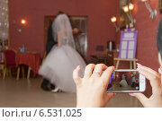 Купить «Свадебный танец молодоженов, гости снимают на камеру мобильного телефона», фото № 6531025, снято 11 октября 2014 г. (c) Сергей Сергеев / Фотобанк Лори