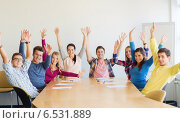 Купить «group of smiling students raising hands in office», фото № 6531889, снято 7 сентября 2014 г. (c) Syda Productions / Фотобанк Лори