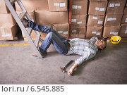 Купить «Worker lying on the floor in warehouse», фото № 6545885, снято 10 мая 2014 г. (c) Wavebreak Media / Фотобанк Лори