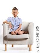 Красивая маленькая девочка в синей клетчатой рубашке сидит на кресле на белом фоне. Стоковое фото, фотограф Сергей Богданов / Фотобанк Лори