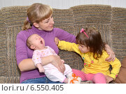 Купить «Трехлетняя девочка отталкивает маму рукой, глядя на маленькую сестренку. Детская ревность», фото № 6550405, снято 12 октября 2014 г. (c) Ирина Борсученко / Фотобанк Лори