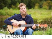 Купить «smiling man playing guitar in camping», фото № 6557081, снято 31 августа 2014 г. (c) Syda Productions / Фотобанк Лори