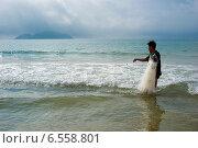 Купить «Китайский рыбак вытаскивает сеть из моря», фото № 6558801, снято 8 февраля 2014 г. (c) Алексей Маринченко / Фотобанк Лори