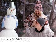 Купить «Счастливая пара рядом со снеговиком», фото № 6563245, снято 16 марта 2014 г. (c) Барковский Семён / Фотобанк Лори